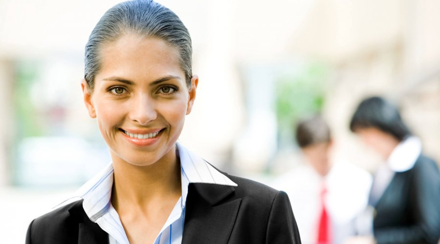 Portrait of pretty employer smiling at camera in working environment