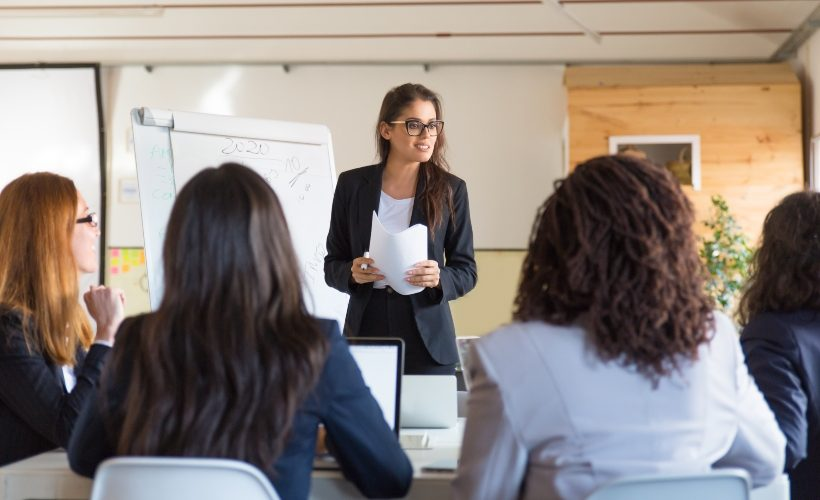 Businesswomen looking at speaker with papers. Group of professional multiethnic businesswomen looking at leader during meeting in office. Women in business concept